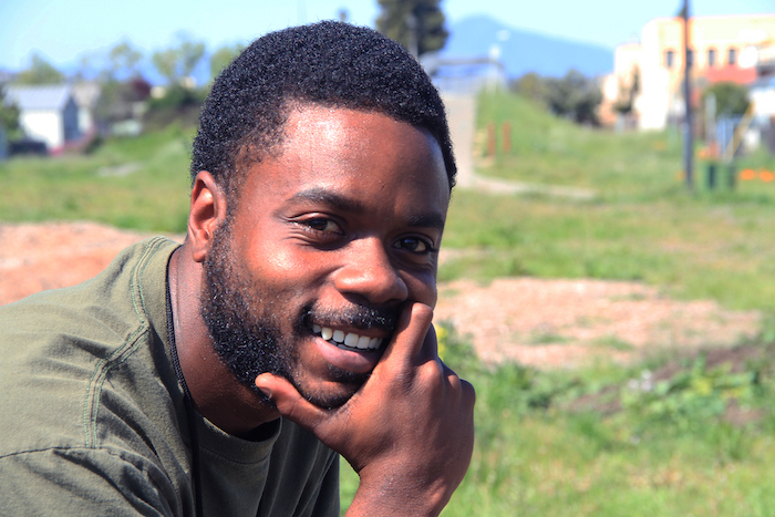 A smiling Black man with his hand on his chin.