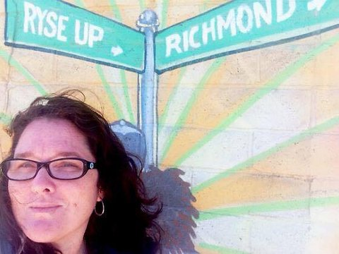 "Kimberly Aceves in front of painting with words ""Rise Up Richmond."""