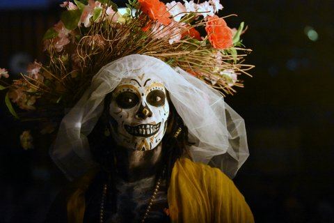 Woman with her face painted like a skull in Dia de Muertos makeup and a floral headdress