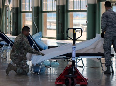 Two men in Army uniforms prepare a hospital bed in Craneway Pavilion.