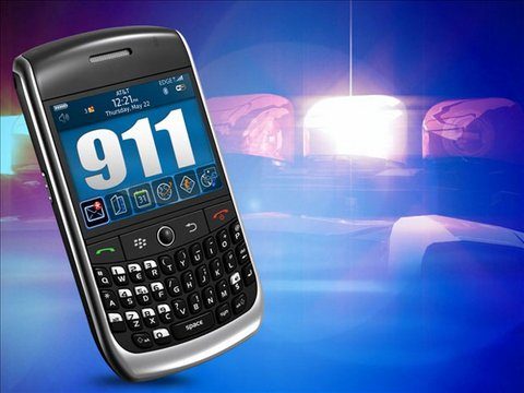 Cellphone with 911 onscreen and police siren backdrop