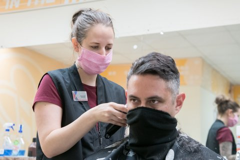 A woman cuts a man's hair with both wearing face coverings.