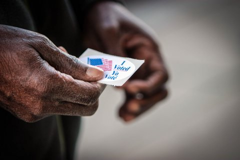 "Close-up of a Black man's hands holding an ""I Voted"" sticker"