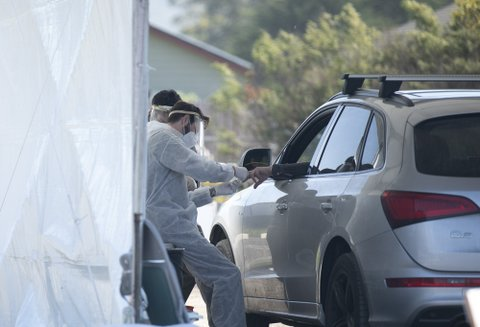 Man in face shield takes finger prick blood sample from hand sticking out of car window.
