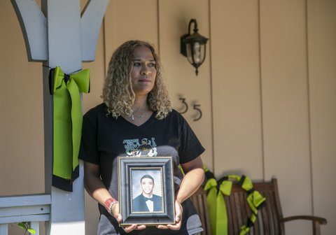 A woman holding a framed photo of her young adult son.