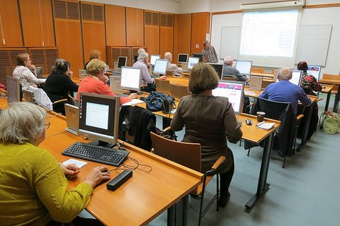 View from behind of older adults at computers in a class.