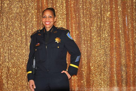 A smiling Black and Latina woman in police uniform in front of sparkly gold curtain.