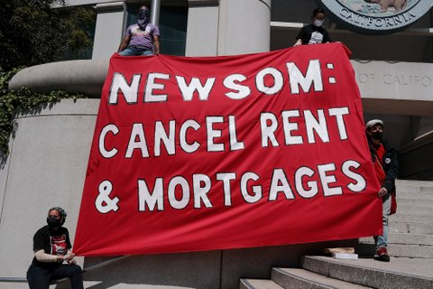 People on steps of government building hold red banner that reads Newsom: Cancel rent & mortgages.