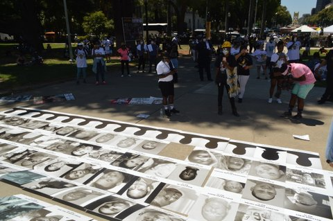 People standing by rows of black-and-white photos laid out on the ground.