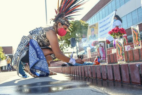 Person in protective mask and Aztec headdress kneels in front of steps with candles and flowers.