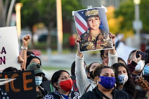 Crowd of protesters in masks. One holding up photo of Vanessa Guillen in Army uniform.
