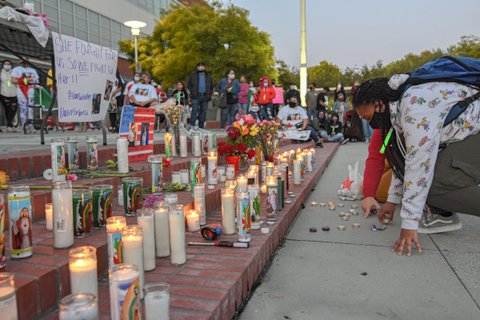 Person in mask kneels next to steps lined with candles