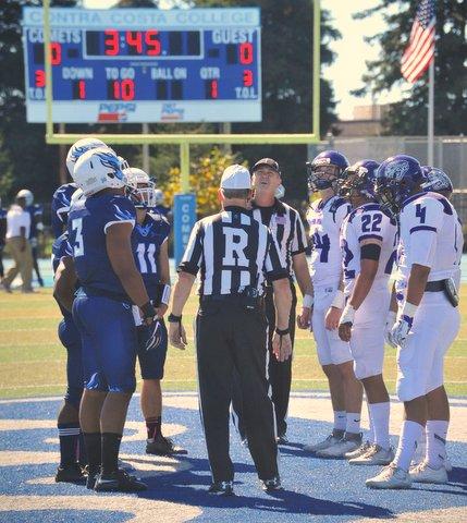 Football players and referees on Contra Costa College field.