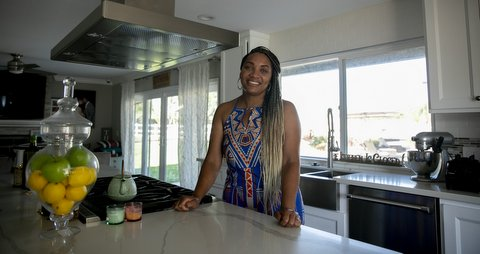 Smiling Black woman with long black and blond braids at kitchen counter.