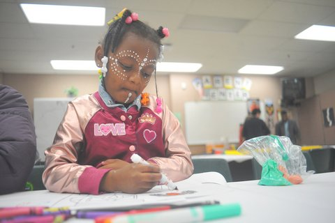 Black girl with rhinestones on her face colors with marker in a classroom.