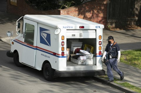 Postal carrier in mask and gloves next to the back of his open mail truck.