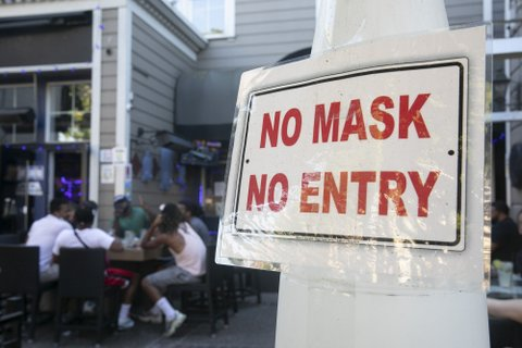 Sign that says NO MASK NO ENTRY in red letters posted at a restaurant with outdoor seating.
