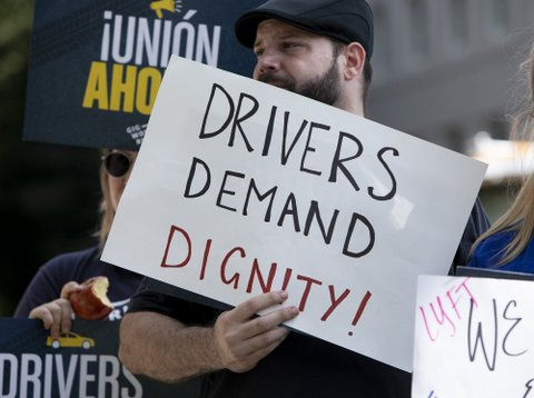 "Man at rally holds sign that says ""Drivers demand dignity!"""