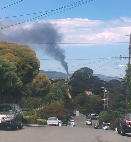 View on a Richmond street of a plume of black smoke in the distance
