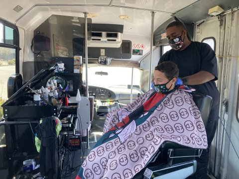 One man cuts another man's hair, both wearing medical masks, in barber chair on a bus