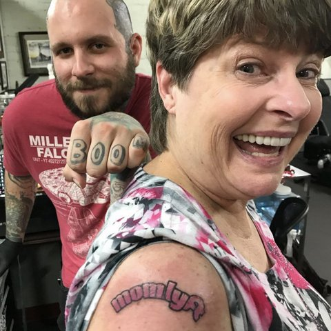 "Woman with pink tattoo that says ""momlyft"" on her bicep and man making fist with ""BOOM"" tattooed on his fingers."