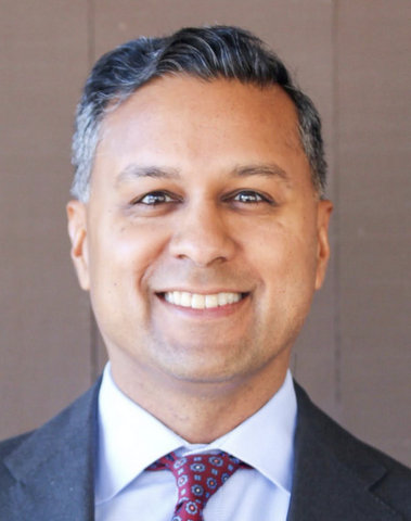A smiling man of Indian descent in suit and tie.