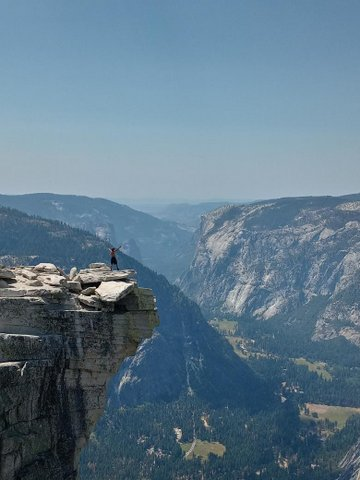 Wide shot of Yosemite with man standing atop Half Dome Mountain with arms raised triumphantly.
