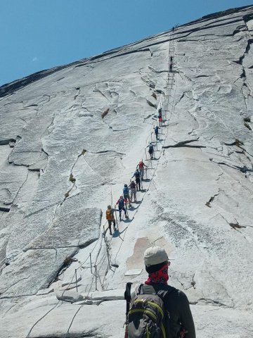 View from behind of man standing at the base of a sheer rock wall that people are using cables to ascend.