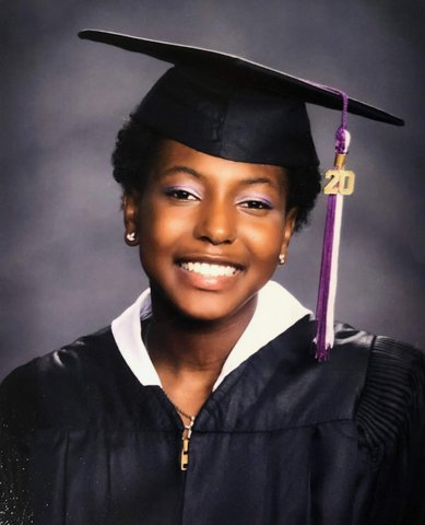 A smiling Black woman in cap and gown with purple and white tassel with the number 20.