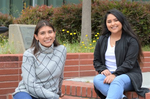 Two smiling young Latina women sitting on brick steps