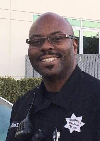 Smiling Black man in glasses and uniform that says Richmond Sergeant Police.