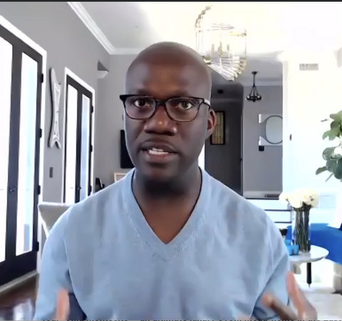A Black man in a light blue V-neck and glasses.