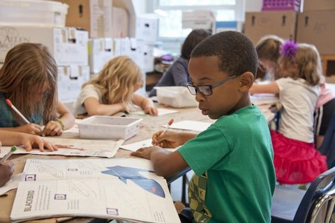 Kids drawing at a table with focus on African American boy in glasses and green shirt.