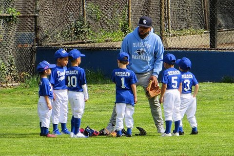 Black man in Yankees cap and Bluebirds Baseball hoodie with kids in baseball uniforms.