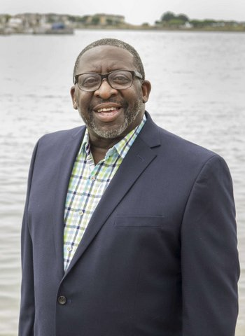A Black man in a suit with no tie and glasses standing in front of a body of water.