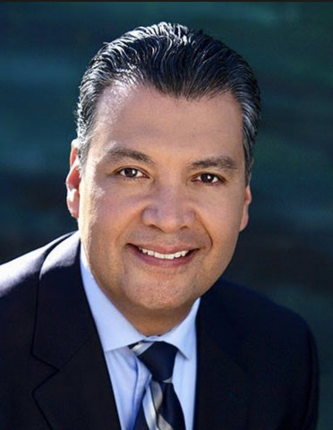A smiling Latino man in dark suit with tie and light-blue shirt.