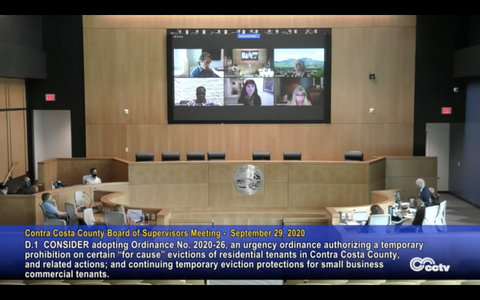 Board of Supervisors meeting with some distanced in government building and others shown on big screen.