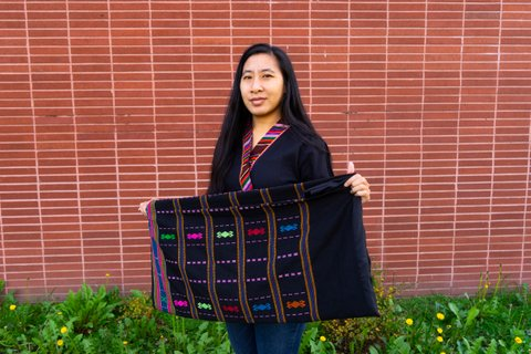 An Asian woman holds a black cloth embroidered with different colors.