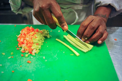 Close up of a Black person's hands cutting thin strips of celery next to a pile of minced carrots and celery.