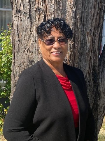 A Black woman wearing tinted glasses, red shirt and black jacket standing in front of a tree.