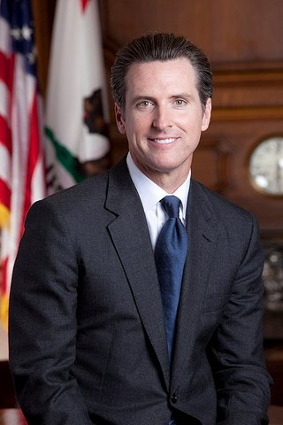 Gavin Newsom, a white man in dark suit with blue tie, with U.S. and California flags over his right shoulder.