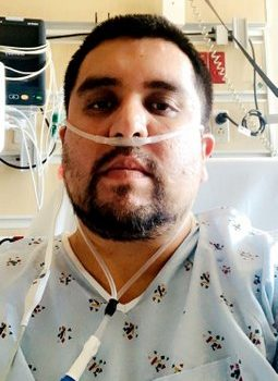 A Latino man in a hospital bed and gown with oxygen tube in his nose.