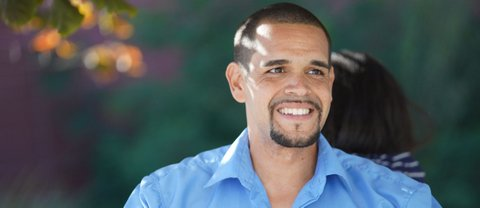 Melvin Willis, a light-skinned Black man with a goatee and light blue shirt.