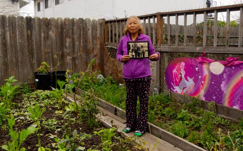 An older Asian woman holding an old photo stands in a garden next to a pink screen with rainbow and unicorn designs.
