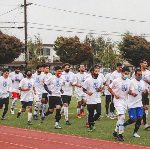 Men in medical-style face masks run on a field.