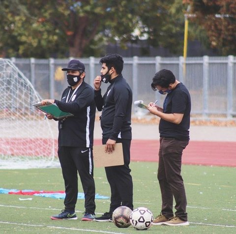 Three men with face masks and clipboards stand near two balls on a soccer field.