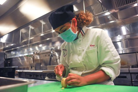 A woman with curly hair, black cap, blue mask and white chef's coat cuts a potato.