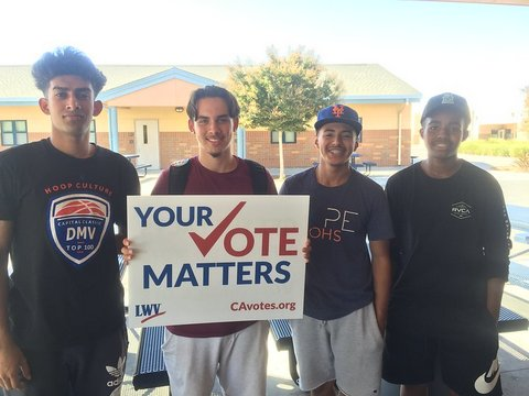 "Four young men with one holding sign that reads ""Your vote matters"" with a checkmark in place of the ""v."" Other text says LWV and CAvotes.org."