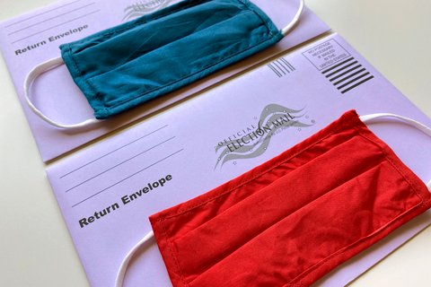 """Two purple envelopes that say """"Official Election Mail,"""" each with a mask laid on top, one red and one blue."""
