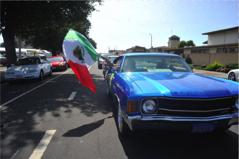 Blue car with Mexican flag being waved out of the front passenger window.